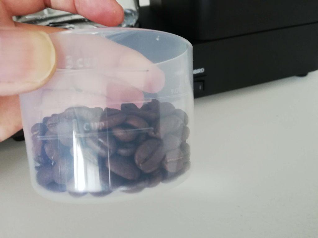 計量カップの豆を入れる